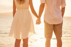 Couple holding hands at sunset on beach. Romantic young couple